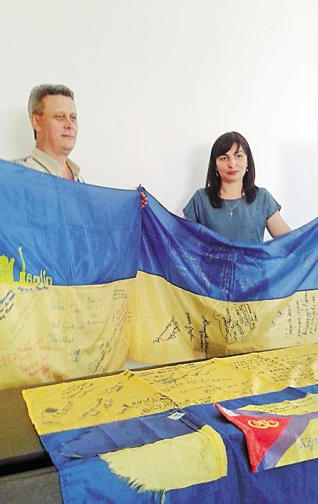 Активісти громадського руху «Очищення» Сергій П'ятниця й Ірина Сафронова демонструють зібрані на блокпостах бойові прапори. Фото автора
