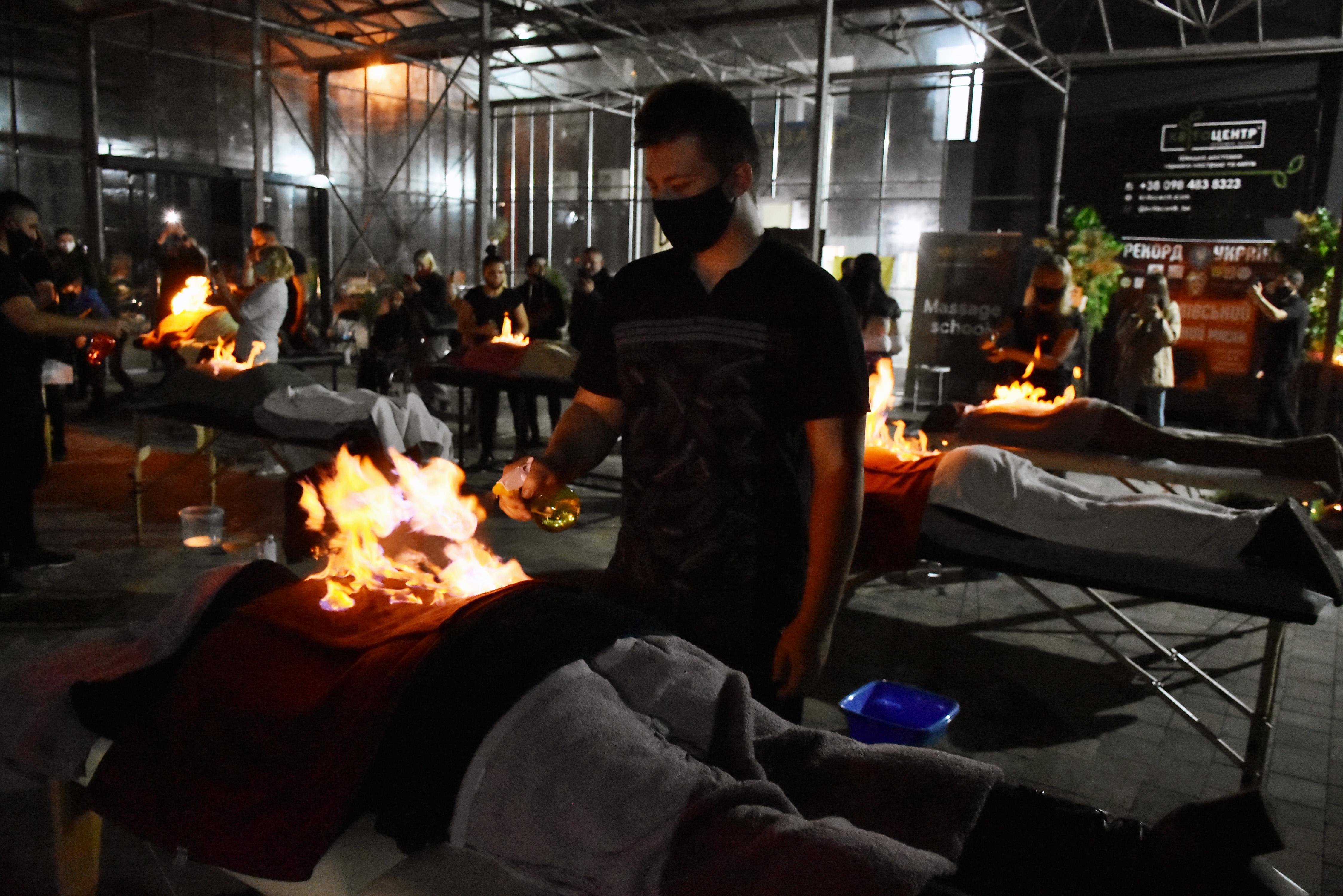 Один з учасників рекордного дійства проводить вогняний масаж